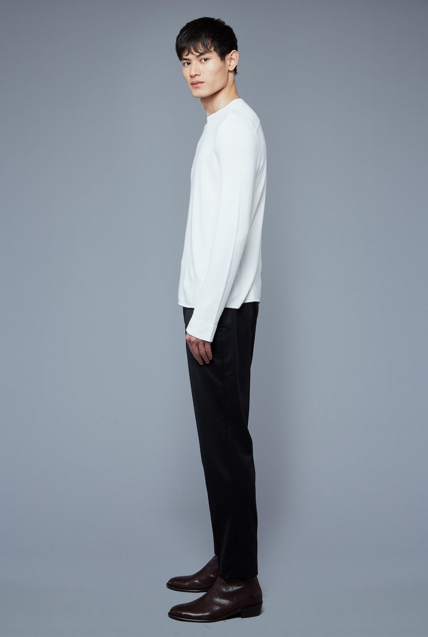 Side View: Model Qiang Li wearing Long Sleeve Sweater Tee