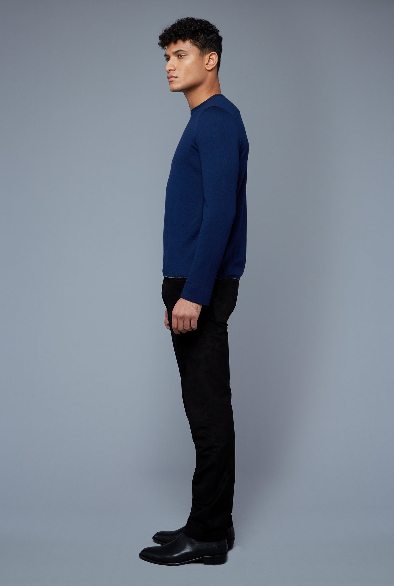 Side View: Model Tre Boutilier wearing Long Sleeve Sweater Tee