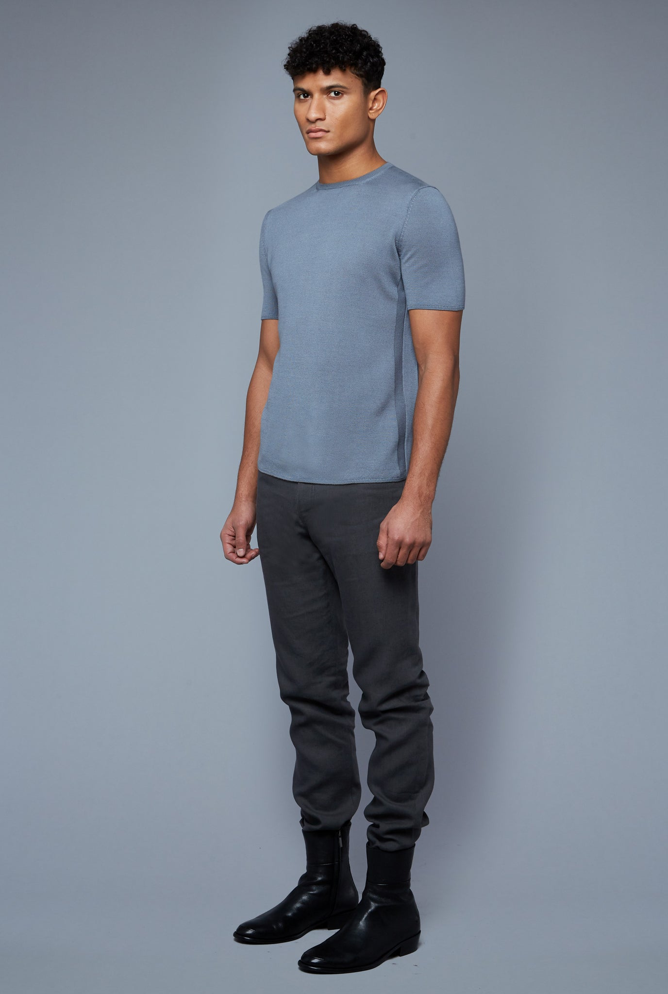 Three Quarter View: Model Tre Boutilier wearing Short Sleeve Sweater Tee