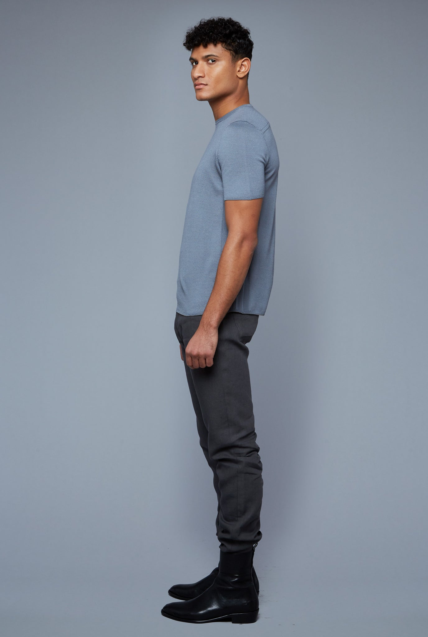 Side View: Model Tre Boutilier wearing Short Sleeve Sweater Tee