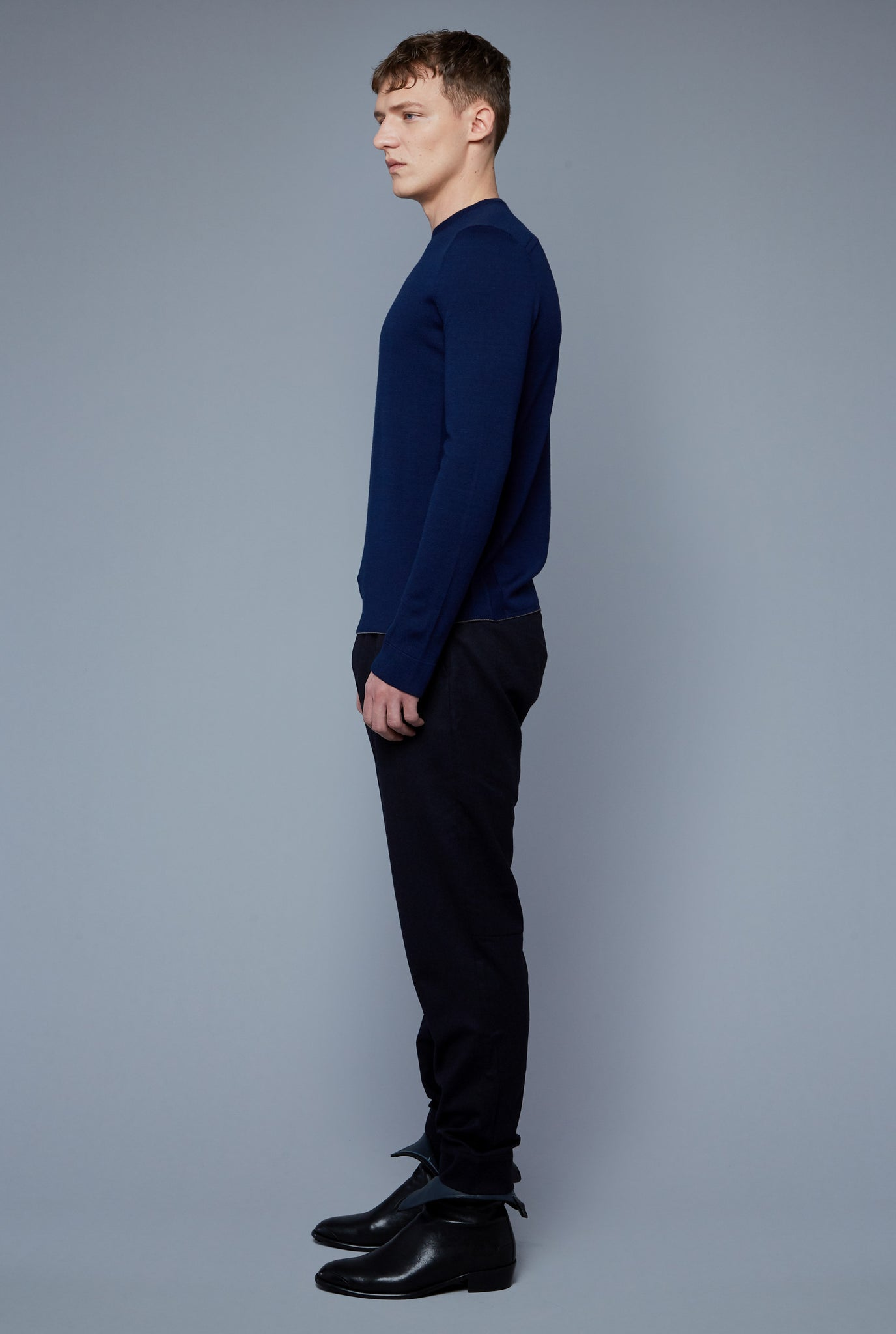 Side View: Model Milos Drago wearing Long Sleeve Sweater Tee
