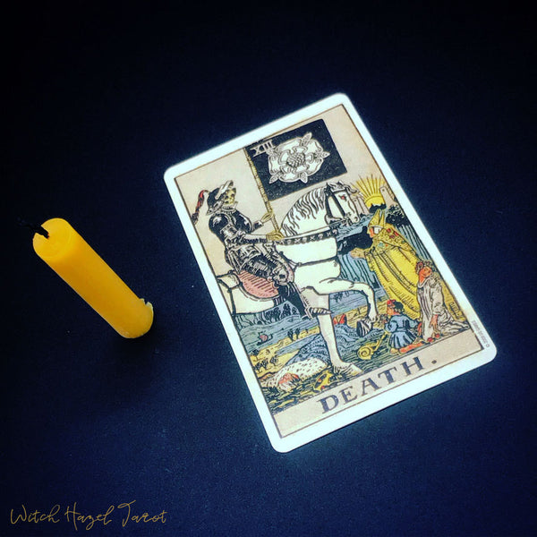 Death tarot card from the Rider-Waite-Smith decks. Detailed card description in body text. Pictured next to a half-burnt beeswax candle on a blue-black background.
