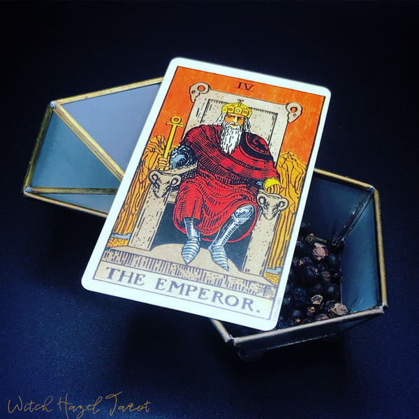The Emperor tarot card. Detailed image description in bio. Card pictured on an open hexagonal box containing dried juniper. Blue-black background.