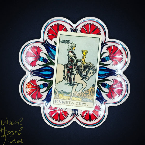 Knight of Cups Tarot Card. Card description in body text. Card pictured at slight angle on flower-shaped decorative tile with vivid red and blue Turkish pattern. Tile sits on deep black background.