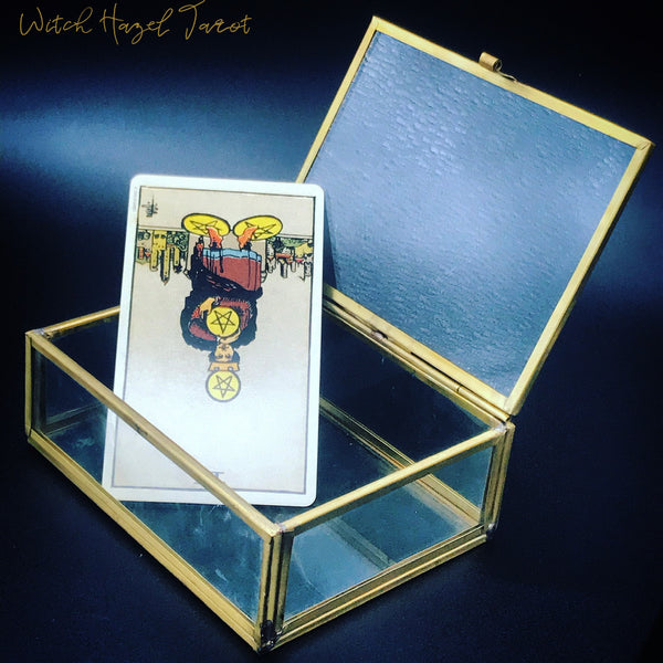 Four of Pentacles Rider-Waite-Smith tarot card reversed, detailed image description in body text, pictured in an open glass box on a dark blue background
