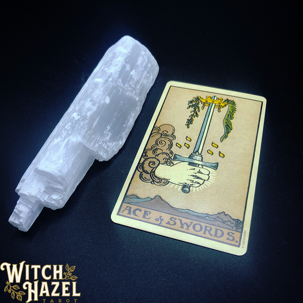 Ace of Swords tarot card from Rider-Waite-Smith deck, pictured with selenite tower on dark blue background, detailed card image description in body text