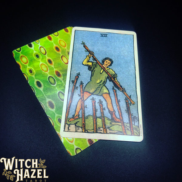 Seven of Wands Rider-Waite tarot card pictured with a Dreaming Way tarot card on a dark background. You can find a detailed image description of the card in the body text of this article.