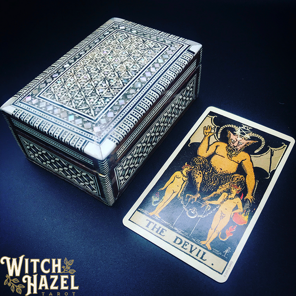 The Devil Rider-Waite tarot card pictured with an ornate bone-inlay box. You'll find a detailed image description of the card in the body text of this post.