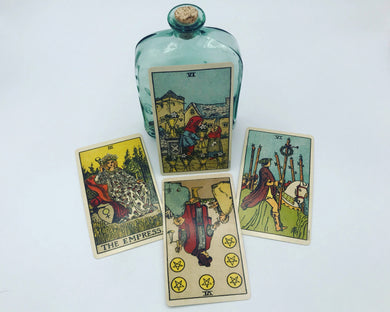 Best friends tarot spread featuring four Rider-Waite-Smith tarot cards and a witchy bottle of magic moon water