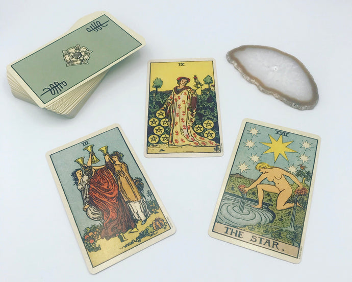 A classic three-card tarot spread preview showing a Rider-Waite-Smith deck and a geode crystal