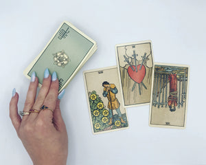 Live online tarot reading preview. Fortune teller's hand with Rider-Waite-Smith deck and a three-card tarot spread