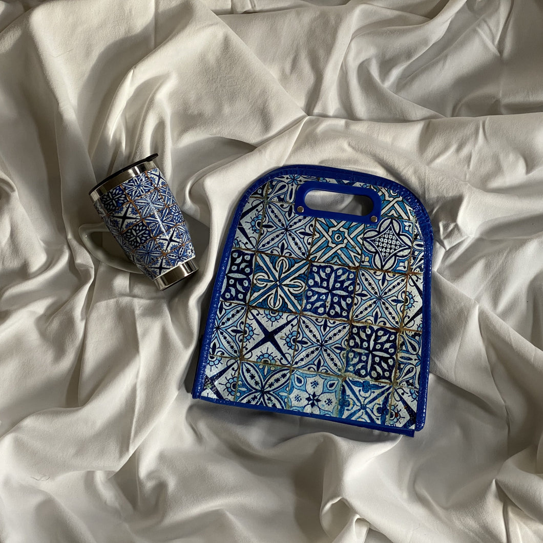 lunch bag with batik traditional indian print in blue, laying on white dreamy sheet with same style mug