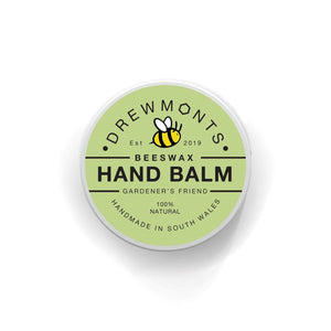A small pot of natural beeswax hand balm in a mint green tin with lovely typography