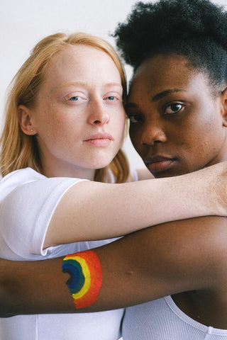 White skin girl hugging a black sking girl who has a rainbow tattoo on her arm