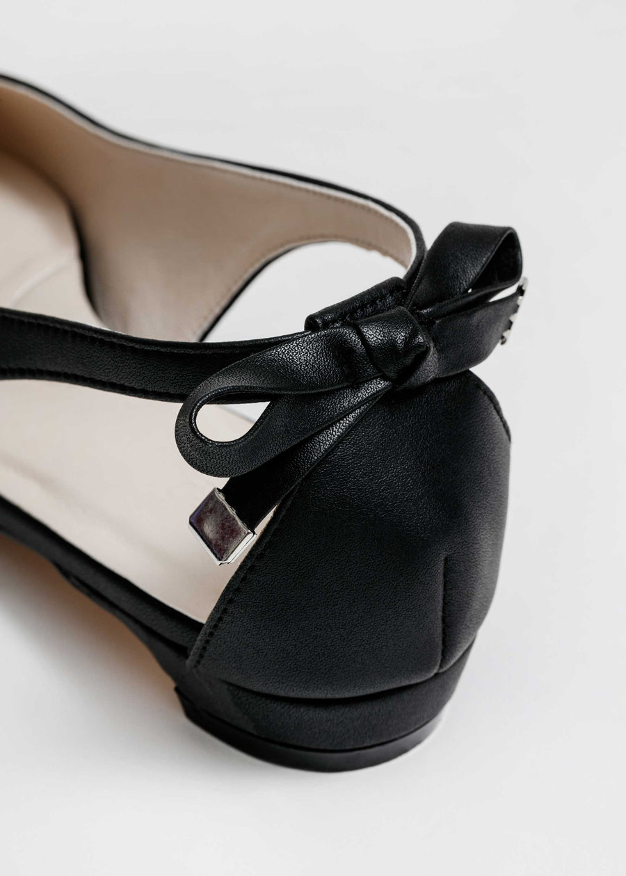 Taffystep The Gummy. Black ballet flats with a subtle pointy toe and a delightful bow detail on the back. Made with a soft microfiber vegan leather and cushioned insole. Deigned in Canada.