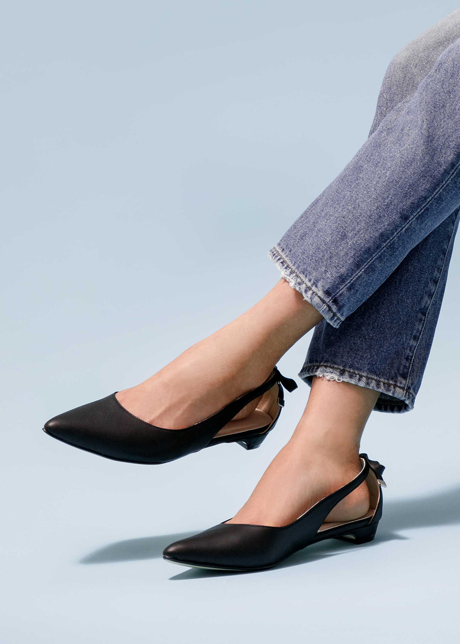 Close up shot of the model in jeans and Taffystep The Gummy. The Black ballet flats with a subtle pointy toe and a delightful bow detail on the back. The shoes is made with a soft microfiber vegan leather and cushioned insole.