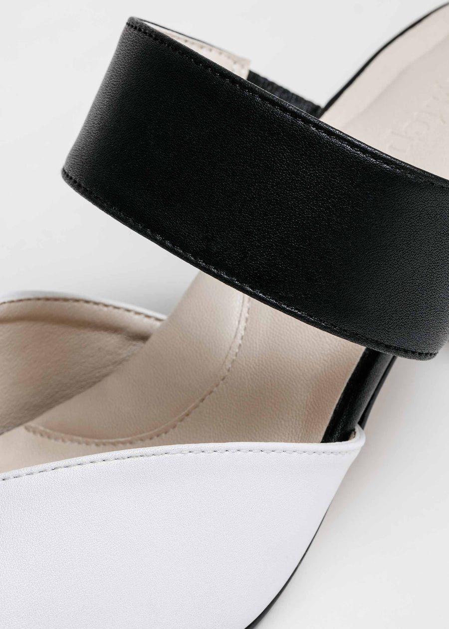 Close up shot. Taffystep The Smartie Mules. Black and white mules with stylish pointy toe, a subtle V-cut opening and a walkable block heel will bring you all-day comfort and takes you from work to play. Made with a soft microfiber vegan leather and cushioned insole. Designed in Vancouver, Canada.