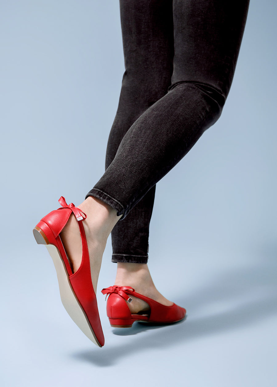 Close up shot of the model in jeans and Taffystep The Gummy. The red ballet flats with a subtle pointy toe and a delightful bow detail on the back. The shoes is made with a soft microfiber vegan leather and cushioned insole.