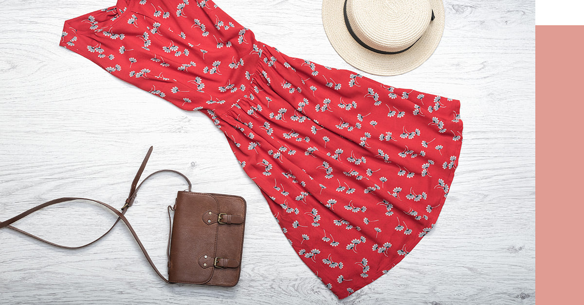 Summer dress with a hat and purse laid out.