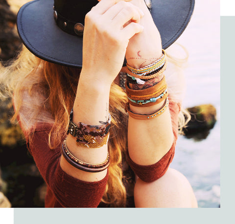 Woman with a boho hat and bracelets sitting by the water.