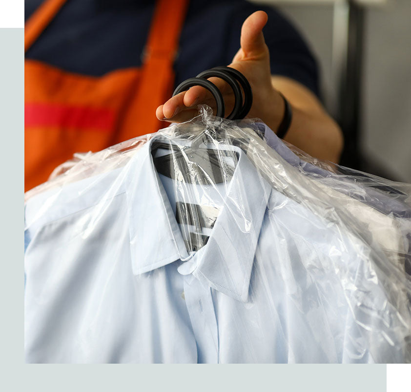 A dry cleaner worker holding shirts covered in plastic.