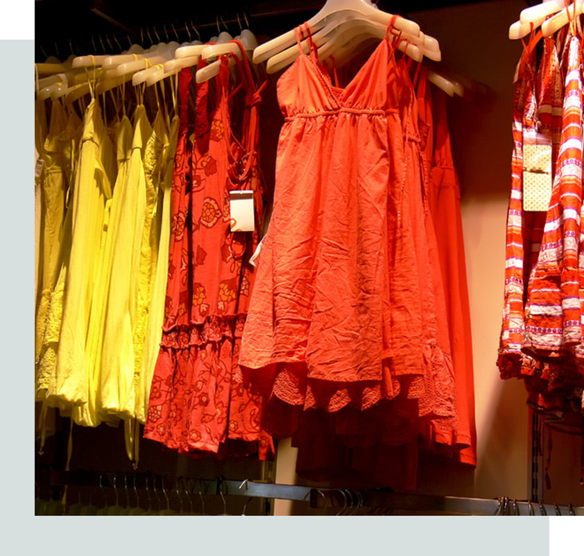 Summer dresses hanging on a rack at a clothing store.