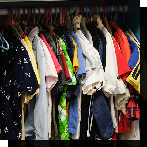 A bunch of shirts hanging in a closet.