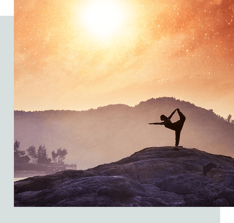Woman doing yoga on a rock beside a river.