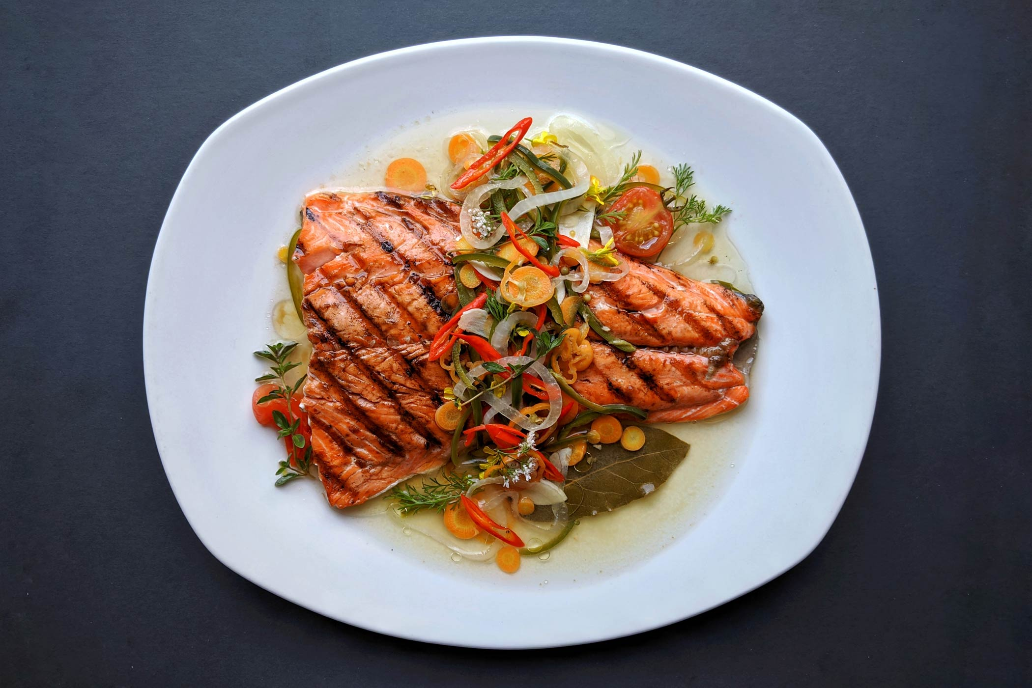 Grilled salmon in sauce topped with vegetables
