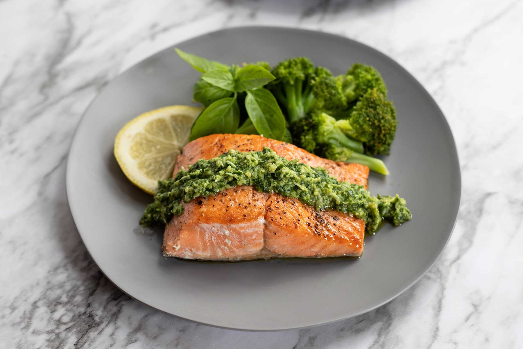Plated dish of mixed herb pesto and coho salmon