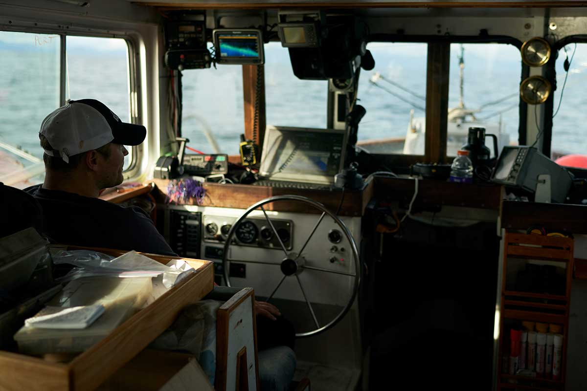 Fisherman steers his boat on the open water