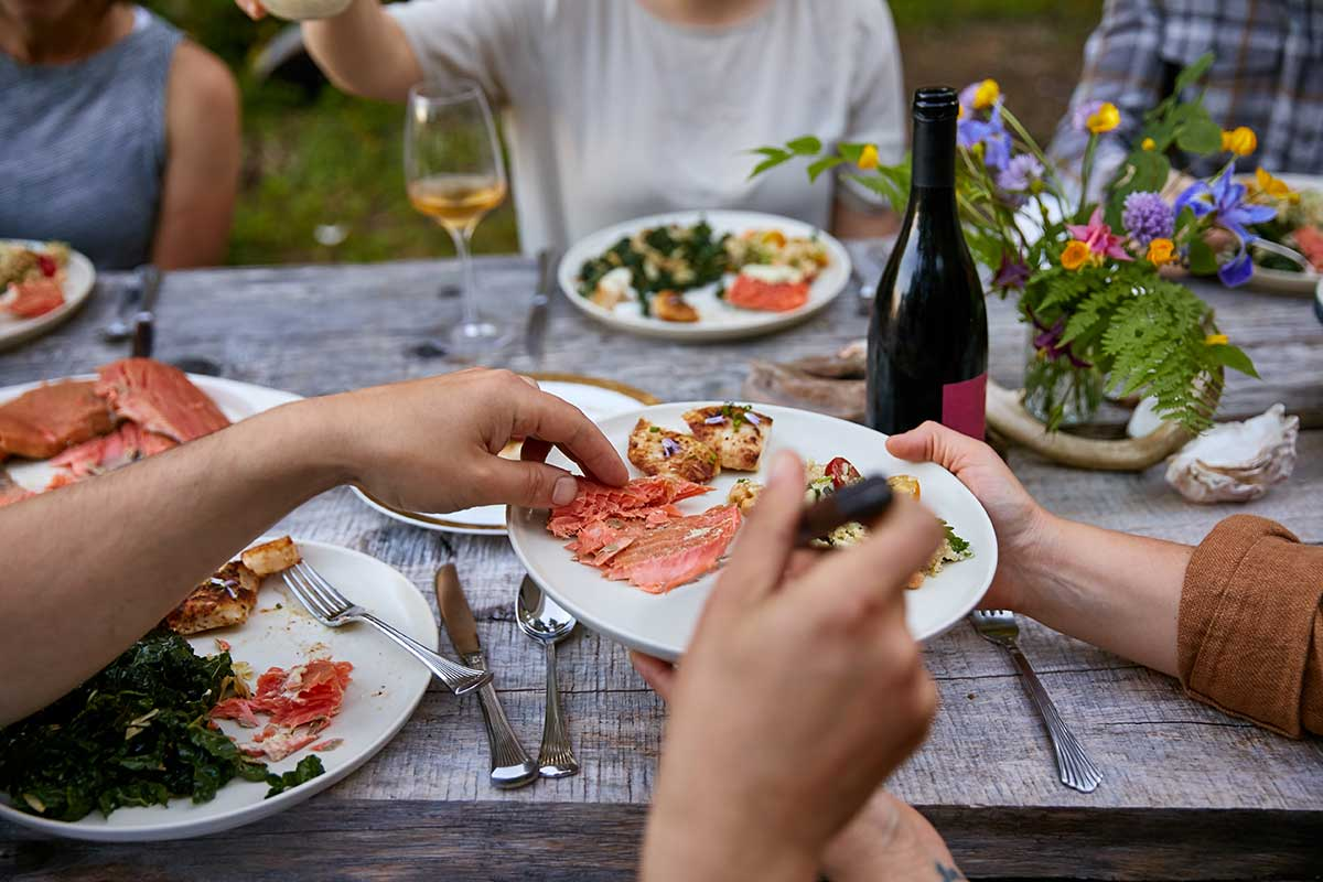 Friends enjoy salmon at a dinner party