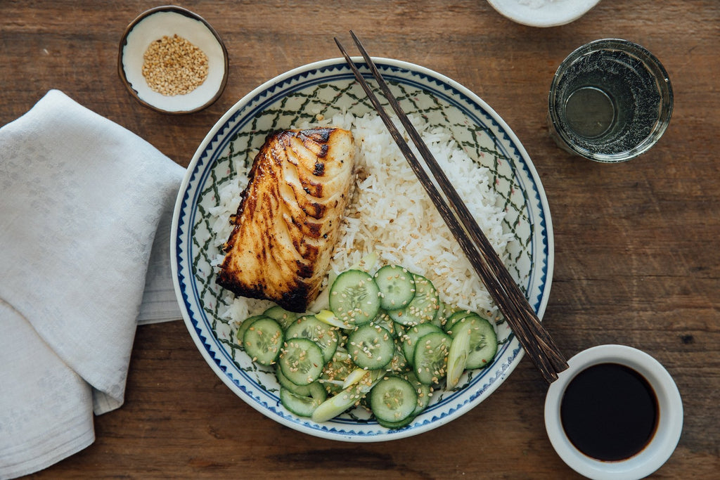 A plated dish of seared sablefish with rice and quick pickles