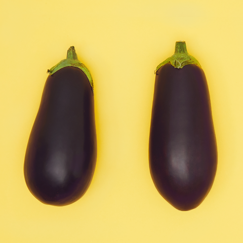 Two aubergines in front of a yellow background