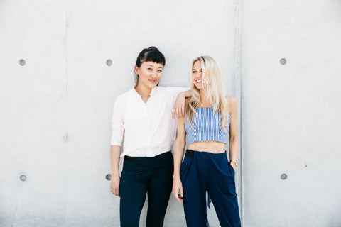 ADAY founders Meg He and Nina Faulhaber posing in front of a concrete wall.