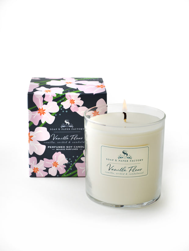 Vanilla Fleur Soy Candle with notes of Vanilla bean, Orchid & Sandalwood.  Glass candle in box designed with our signature look, whimsy pinkish orchids on bold navy background. Candle burns 65  hours and is made in NY. Made in USA.