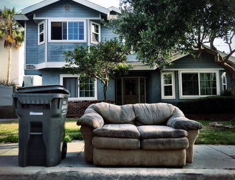 couch on curb next to trash can