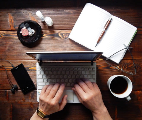 Freelancer Working At Desk With Computer And Notepad
