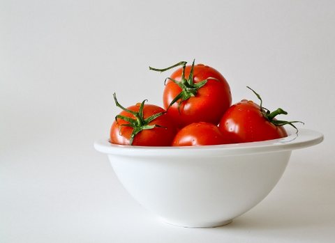 Tomatoes are a source of vitamin E. Tomatoes in a white bowl
