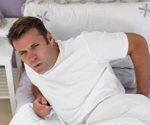 man laid in bed with back ache needs a posture corrector for men