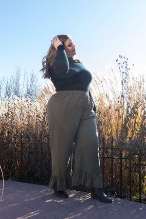 plus size model wearing khaki green pants with a gathered hem detail and black turtleneck in a public park