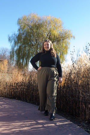 blonde woman walking on a stone path in the park wearing green loose fitting pants and a black turtleneck