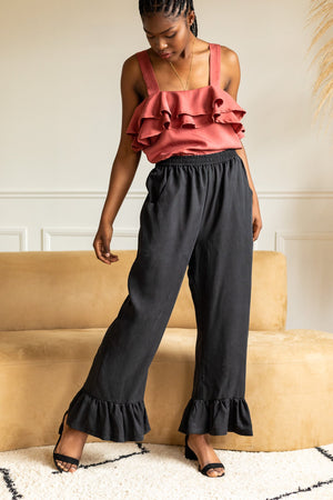 female model standing with her legs apart while looking down, wearing black flowy pants and a soft red tank top with ruffle details