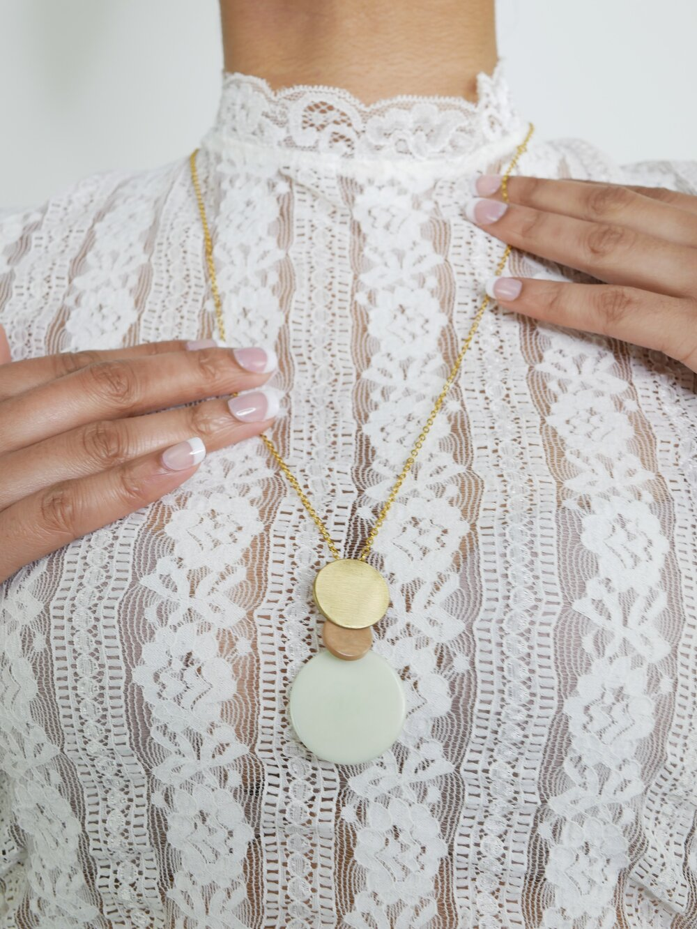 Woman wearing the overlapping tagua disc pendant and chain necklace over a white top