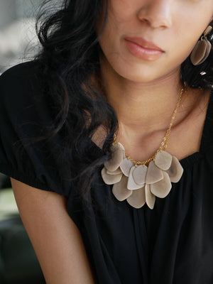 Woman alluringly stands out wearing a matching neutral Stone treasure earrings and necklace over a black top