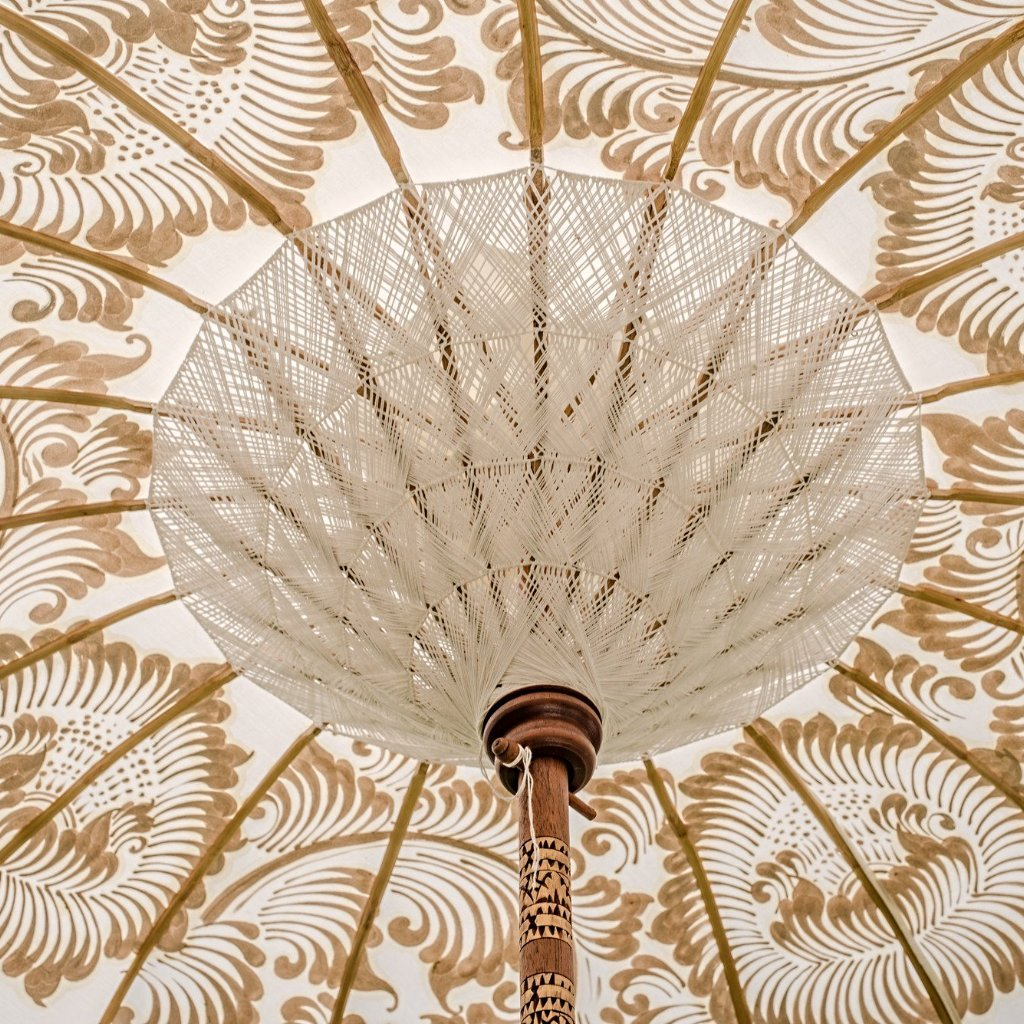 Simone- Cream white and gold garden handmade parasol with fringing pom poms and beads. A Bali umbrella perfect for a picnic, patio, through your table with an umbrella hole or by your sun lounger at the pool. Make your outdoor space chic, elegant and glamorous with this chic boho garden accessory. The most pretty and elegant garden umbrella. Luxury garden decoration for a fabulous summer.