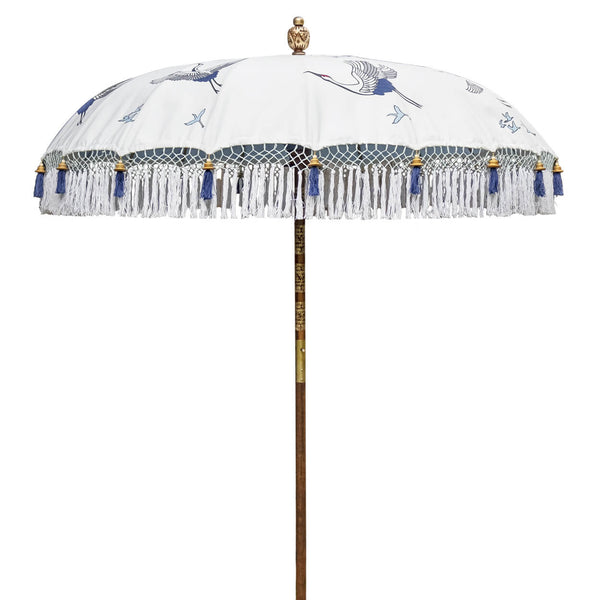 East London Parasol Lexi -blue and white printed soaring cranes garden parasol with tassels in shades of white, hand made. The perfect garden umbrella for picnics, gardens, summer, patios, pool side and terraces. Bali and Indian inspired garden parasol and luxurious designer garden feature.