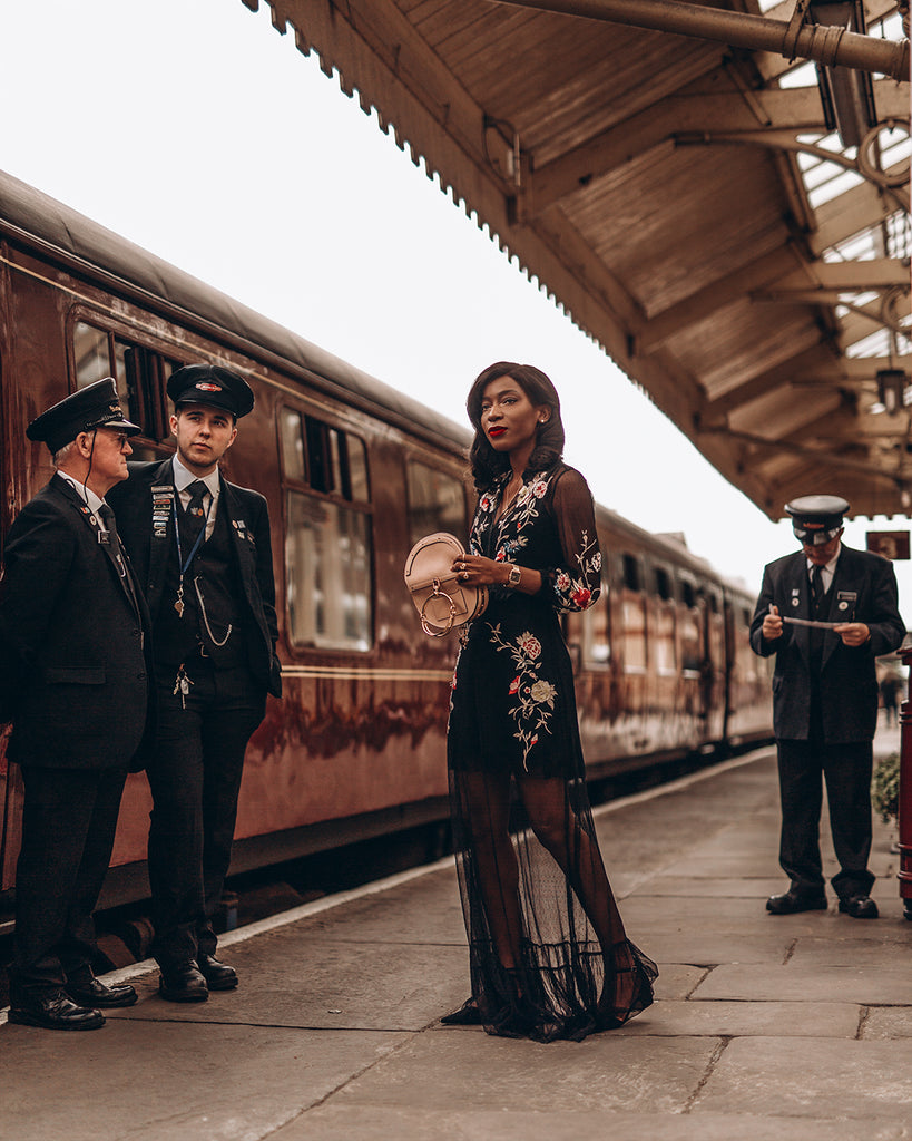 Onyi Moss - self-taught photographer posing on a train platform