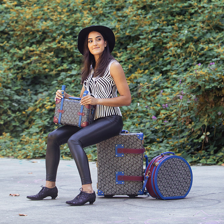 Woman sitting with Fluevog x SteamLine Luggage collaboration collection