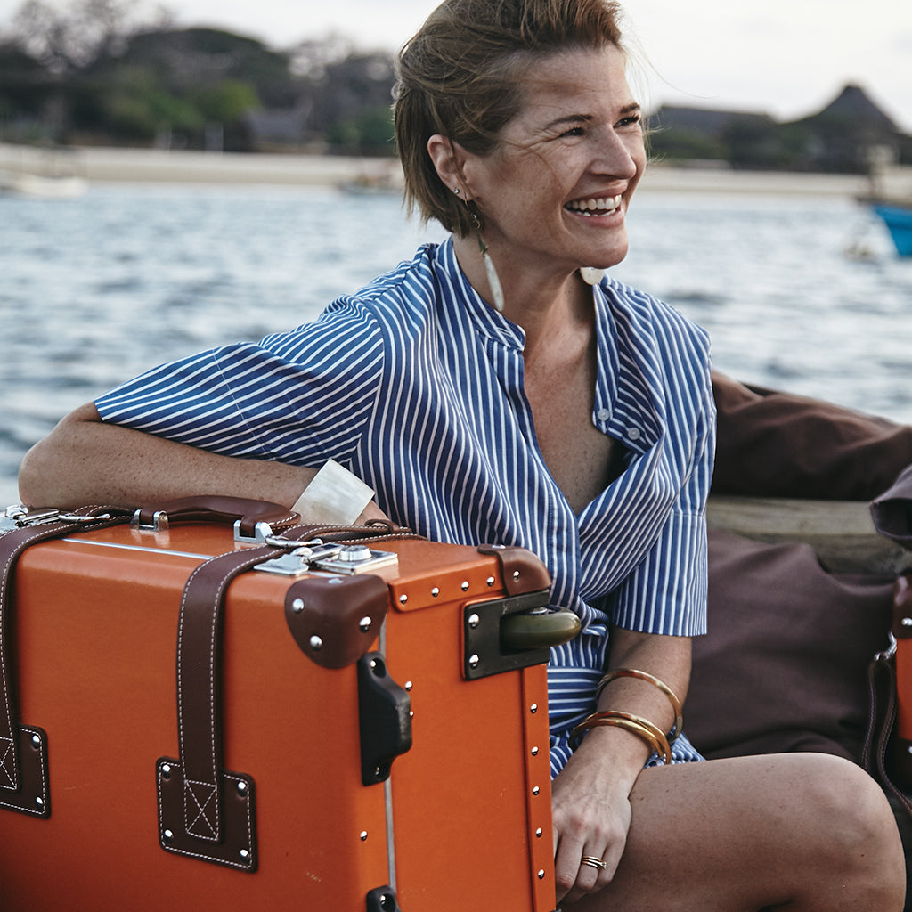 SteamLine Luggage founder Sara Banks with her Orange Anthropologist Stowaway, during her time in Lamu, Kenya